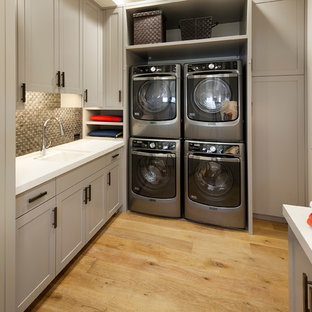 Dedicated laundry room - mid-sized mediterranean u-shaped light wood floor dedicated laundry room idea in Santa Barbara with an undermount sink, shaker cabinets, gray cabinets, solid surface countertops, white walls, a stacked washer/dryer and white countertops