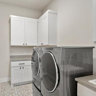 Foto på en mellanstor lantlig grå l-formad tvättstuga enbart för tvätt, med en nedsänkt diskho, skåp i shakerstil, vita skåp, bänkskiva i kvarts, grått stänkskydd, grå väggar, klinkergolv i keramik, en tvättmaskin och torktumlare bredvid varandra och beiget golv