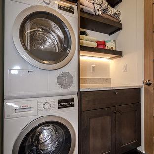 Exempel på en liten modern vita linjär vitt tvättstuga enbart för tvätt, med skåp i shakerstil, skåp i mörkt trä, bänkskiva i kvarts, vita väggar, laminatgolv, en tvättpelare och brunt golv