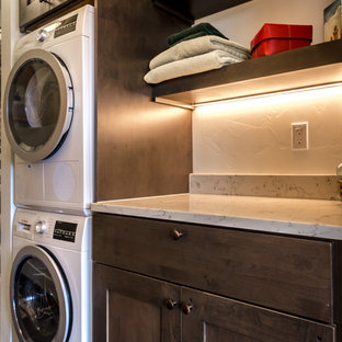 Small modern single-wall dedicated laundry room in Denver with shaker cabinets, dark wood cabinets, quartz benchtops, white walls, laminate floors, a stacked washer and dryer, brown floor and white benchtop.