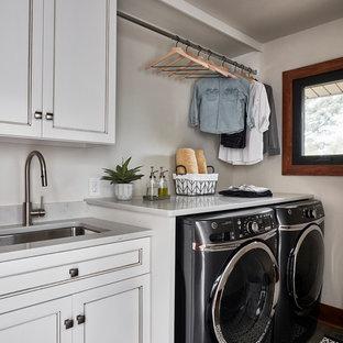 Idéer för en mellanstor rustik vita linjär tvättstuga, med en undermonterad diskho, luckor med infälld panel, vita skåp, bänkskiva i kvarts, vita väggar, klinkergolv i porslin, en tvättmaskin och torktumlare bredvid varandra och grått golv