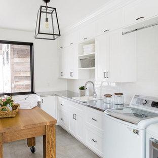 Ispirazione per una lavanderia tradizionale con lavello da incasso, ante bianche, top in acciaio inossidabile, pareti bianche e ante in stile shaker