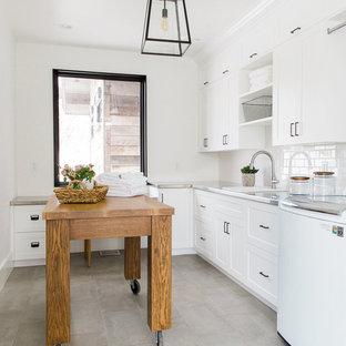 Inspiration pour une buanderie traditionnelle avec un évier posé, un placard à porte plane, des portes de placard blanches, un plan de travail en inox et un mur blanc.