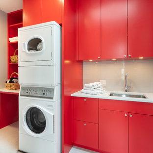 Inspiration for a mid-sized contemporary single-wall porcelain tile and white floor dedicated laundry room remodel in Providence with an undermount sink, flat-panel cabinets, red cabinets, quartz countertops, gray walls, a stacked washer/dryer and white countertops