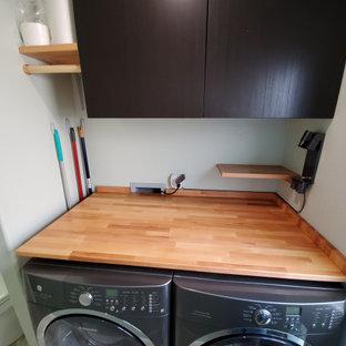 Idee per una piccola lavanderia multiuso moderna con ante lisce, ante in legno bruno, top in legno, paraspruzzi marrone, paraspruzzi in legno, pareti verdi, pavimento con piastrelle in ceramica, lavatrice e asciugatrice affiancate, pavimento multicolore e top marrone