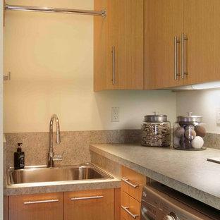 Foto på en mellanstor funkis tvättstuga enbart för tvätt, med en nedsänkt diskho, skåp i mellenmörkt trä, beige väggar och en tvättmaskin och torktumlare bredvid varandra