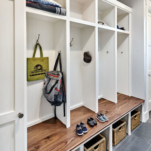 This is an example of a mid-sized transitional galley utility room in San Francisco with an utility sink, shaker cabinets, white cabinets, quartz benchtops, grey walls, porcelain floors and a side-by-side washer and dryer.