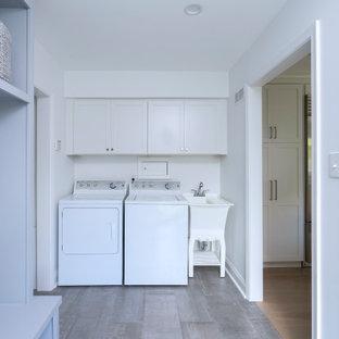 Esempio di una piccola lavanderia multiuso moderna con lavatoio, ante in stile shaker, ante bianche, pareti bianche, pavimento con piastrelle in ceramica, lavatrice e asciugatrice affiancate e pavimento grigio