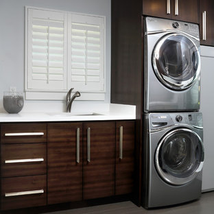 Inspiration for a large modern single-wall dedicated laundry room in San Francisco with an undermount sink, flat-panel cabinets, distressed cabinets, quartz benchtops, grey walls, dark hardwood floors, a stacked washer and dryer and white benchtop.