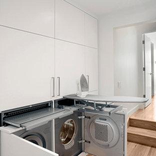 Inredning av en modern liten liten tvättstuga, med släta luckor, vita skåp, vita väggar, mellanmörkt trägolv och en tvättmaskin och torktumlare bredvid varandra