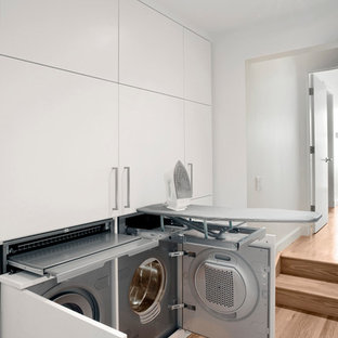 Idee per un piccolo ripostiglio-lavanderia contemporaneo con ante lisce, ante bianche, pareti bianche, pavimento in legno massello medio e lavatrice e asciugatrice affiancate