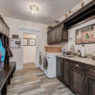 Ispirazione per una lavanderia multiuso classica di medie dimensioni con lavello sottopiano, ante con riquadro incassato, ante in legno bruno, pareti beige, parquet scuro, lavatrice e asciugatrice affiancate, pavimento marrone, top beige e top in granito