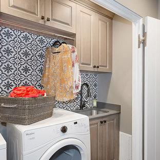 Idee per un piccolo ripostiglio-lavanderia chic con lavello sottopiano, ante con bugna sagomata, ante beige, top in granito, pareti beige, pavimento in legno massello medio, lavatrice e asciugatrice affiancate e pavimento marrone