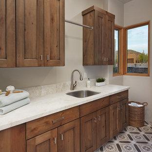 Idéer för en mellanstor vita l-formad tvättstuga enbart för tvätt, med en undermonterad diskho, luckor med infälld panel, bänkskiva i kvartsit, beige väggar, betonggolv, en tvättmaskin och torktumlare bredvid varandra, brunt golv och skåp i mellenmörkt trä