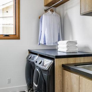 Exempel på en mellanstor modern svarta linjär svart tvättstuga enbart för tvätt, med en undermonterad diskho, släta luckor, skåp i ljust trä, bänkskiva i täljsten, vita väggar, klinkergolv i keramik, en tvättmaskin och torktumlare bredvid varandra och flerfärgat golv
