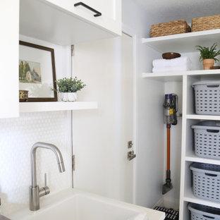 Immagine di una lavanderia multiuso scandinava di medie dimensioni con lavello da incasso, ante in stile shaker, ante bianche, top in legno, pareti bianche, pavimento in gres porcellanato, lavatrice e asciugatrice affiancate, pavimento nero e top marrone