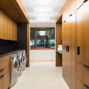 Photo of a large modern galley utility room in New York with a double-bowl sink, flat-panel cabinets, medium wood cabinets, granite worktops and a side by side washer and dryer.