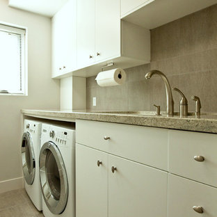 Photo of a large modern galley separated utility room in Los Angeles with a submerged sink, flat-panel cabinets, white cabinets, granite worktops, grey walls, porcelain flooring, a side by side washer and dryer and grey floors.