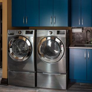 Inspiration för rustika linjära grått grovkök, med en undermonterad diskho, släta luckor, blå skåp, bänkskiva i kvarts, orange väggar, klinkergolv i porslin, en tvättmaskin och torktumlare bredvid varandra och brunt golv