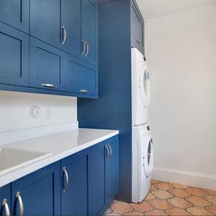 Foto di una sala lavanderia chic di medie dimensioni con lavello da incasso, ante in stile shaker, ante blu, top in superficie solida, pareti bianche, pavimento in terracotta e lavatrice e asciugatrice a colonna