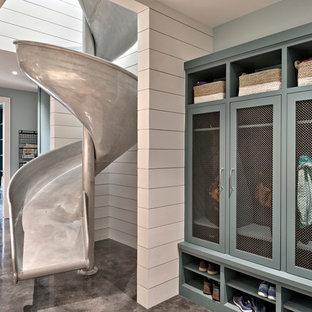 Idee per un'ampia lavanderia multiuso country con ante blu, top in quarzo composito, pareti blu, pavimento in cemento, lavatrice e asciugatrice affiancate e ante in stile shaker