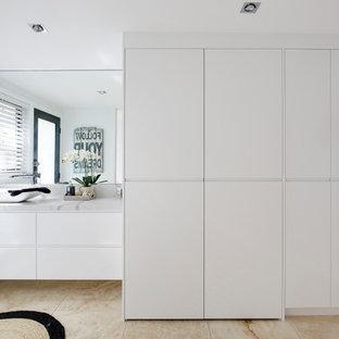 Inspiration för ett mellanstort funkis flerfärgad parallellt flerfärgat grovkök, med en enkel diskho, släta luckor, vita skåp, bänkskiva i kvarts, flerfärgad stänkskydd, vita väggar, travertin golv, tvättmaskin och torktumlare byggt in i ett skåp och flerfärgat golv