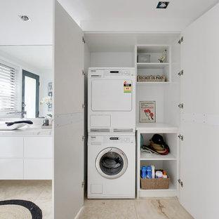 Bild på ett mellanstort maritimt flerfärgad parallellt flerfärgat grovkök, med en enkel diskho, släta luckor, vita skåp, bänkskiva i kvarts, flerfärgad stänkskydd, vita väggar, travertin golv, tvättmaskin och torktumlare byggt in i ett skåp och flerfärgat golv