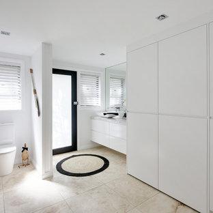 Idéer för ett mellanstort modernt flerfärgad parallellt grovkök, med en enkel diskho, släta luckor, vita skåp, bänkskiva i kvarts, flerfärgad stänkskydd, vita väggar, travertin golv, tvättmaskin och torktumlare byggt in i ett skåp och flerfärgat golv