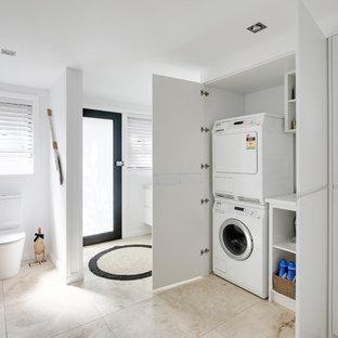 Inspiration för ett mellanstort maritimt flerfärgad parallellt flerfärgat grovkök, med en enkel diskho, släta luckor, vita skåp, bänkskiva i kvarts, flerfärgad stänkskydd, vita väggar, travertin golv, tvättmaskin och torktumlare byggt in i ett skåp och flerfärgat golv
