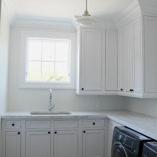 Aménagement d'une buanderie moderne avec un évier encastré, un placard à porte shaker, des portes de placard blanches, un plan de travail en marbre, un mur blanc, un sol en carreau de terre cuite et des machines côte à côte.