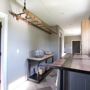 Exemple d'une petite buanderie parallèle moderne multi-usage avec un évier encastré, un placard à porte plane, des portes de placard en bois brun, un plan de travail en bois, un mur gris, un sol en carrelage de céramique et des machines côte à côte.