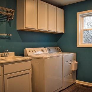 Inredning av en lantlig mellanstor flerfärgade linjär flerfärgat tvättstuga enbart för tvätt, med skåp i shakerstil, blått stänkskydd, stänkskydd i glaskakel, vinylgolv, brunt golv, en nedsänkt diskho, vita skåp, blå väggar och en tvättmaskin och torktumlare bredvid varandra