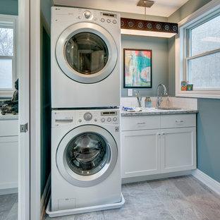 Foto di una piccola sala lavanderia tradizionale con lavello sottopiano, ante in stile shaker, ante bianche, top in quarzo composito, pavimento in gres porcellanato, lavatrice e asciugatrice a colonna, pavimento grigio e pareti blu