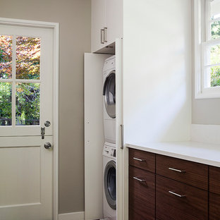 Inredning av en modern liten linjär liten tvättstuga, med släta luckor, vita skåp, grå väggar, mörkt trägolv och en tvättpelare