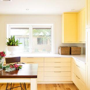 Cette image montre une buanderie vintage multi-usage avec des portes de placard jaunes, un plan de travail en quartz, un mur blanc, un sol en bois clair et des machines dissimulées.