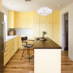 Immagine di una lavanderia multiuso moderna con ante gialle, top in quarzite, pareti bianche, parquet chiaro, lavatrice e asciugatrice nascoste, ante in stile shaker, pavimento marrone e top bianco