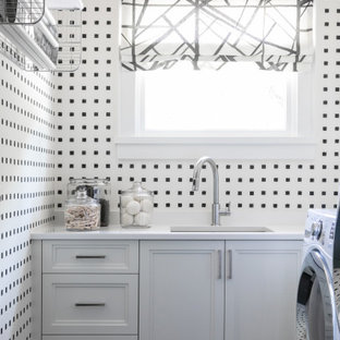 Inspiration for a transitional l-shaped black floor and wallpaper dedicated laundry room remodel in Atlanta with an undermount sink, recessed-panel cabinets, white cabinets, multicolored walls and white countertops