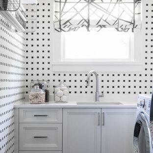 Cette photo montre une buanderie chic en L dédiée avec un évier encastré, un placard avec porte à panneau encastré, des portes de placard blanches, un mur multicolore, un sol noir, un plan de travail blanc et du papier peint.