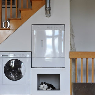Diseño de lavadero bohemio con paredes blancas y lavadora y secadora juntas