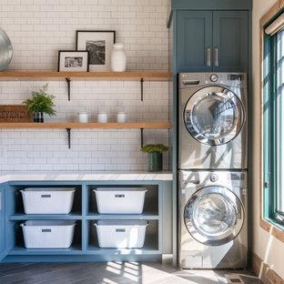 Bild på en stor rustik vita l-formad vitt tvättstuga enbart för tvätt, med en undermonterad diskho, öppna hyllor, blå skåp, vita väggar, en tvättpelare och grått golv