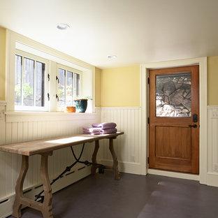 Exempel på en liten amerikansk tvättstuga, med gula väggar, en tvättmaskin och torktumlare bredvid varandra, vita skåp, träbänkskiva och betonggolv