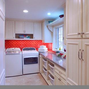 Idée de décoration pour une buanderie bohème en L dédiée avec des portes de placard blanches, un mur rouge, un sol en travertin, des machines côte à côte et un placard avec porte à panneau encastré.