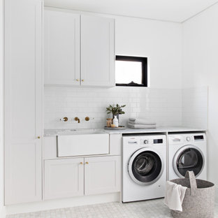 Scandinavian single-wall laundry room in Sydney with a farmhouse sink, shaker cabinets, white cabinets, white walls, marble floors, a side-by-side washer and dryer, white floor and grey benchtop.