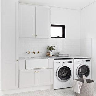Exempel på en minimalistisk grå linjär grått tvättstuga, med en rustik diskho, skåp i shakerstil, vita skåp, vita väggar, marmorgolv, en tvättmaskin och torktumlare bredvid varandra och vitt golv