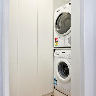 Idéer för en liten nordisk vita l-formad tvättstuga enbart för tvätt, med släta luckor, vita skåp, laminatbänkskiva, vita väggar, klinkergolv i porslin och orange golv