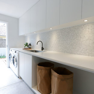 Modern dedicated laundry room in Sydney with an undermount sink, flat-panel cabinets, white cabinets, a side-by-side washer and dryer, grey floor and white benchtop.
