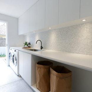 Exempel på en modern vita vitt tvättstuga enbart för tvätt, med en undermonterad diskho, släta luckor, vita skåp, en tvättmaskin och torktumlare bredvid varandra och grått golv