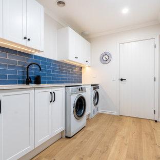 Idéer för stora maritima parallella vitt tvättstugor enbart för tvätt, med en undermonterad diskho, skåp i shakerstil, vita skåp, bänkskiva i kvarts, blått stänkskydd, stänkskydd i tunnelbanekakel, beige väggar, laminatgolv, en tvättmaskin och torktumlare bredvid varandra och beiget golv