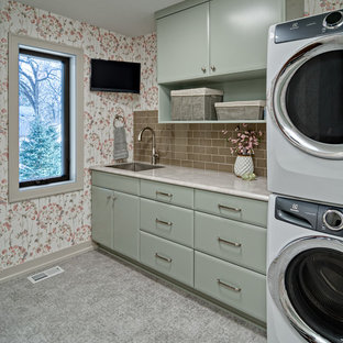 This is an example of a medium sized classic galley separated utility room in Minneapolis with a submerged sink, flat-panel cabinets, green cabinets, laminate countertops, multi-coloured walls, vinyl flooring, a stacked washer and dryer, grey floors and grey worktops.