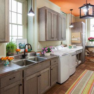 Immagine di una grande sala lavanderia boho chic con lavello a doppia vasca, ante in stile shaker, ante in legno scuro, top in acciaio inossidabile, pareti bianche, pavimento in mattoni, lavatrice e asciugatrice affiancate e pavimento rosso